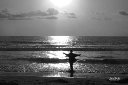 A black and white sunset photo of a woman on a beach